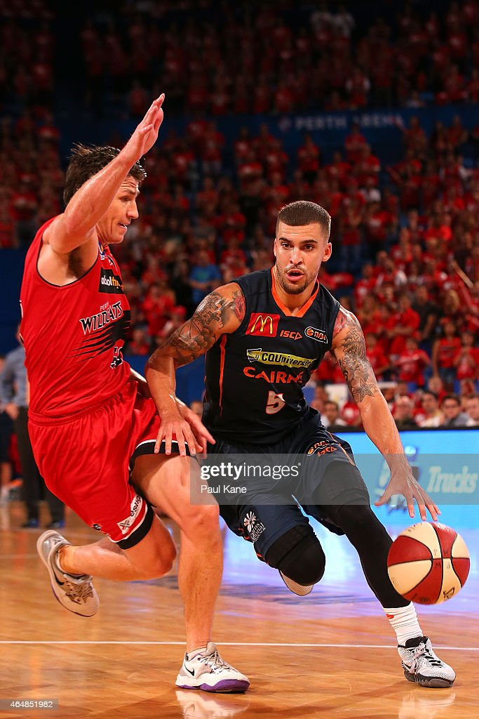 Scottie Wilbekin of the Taipans drives to the basket against Damian Martin of the Wildcats during game two of the NBL Finals series between the Perth...