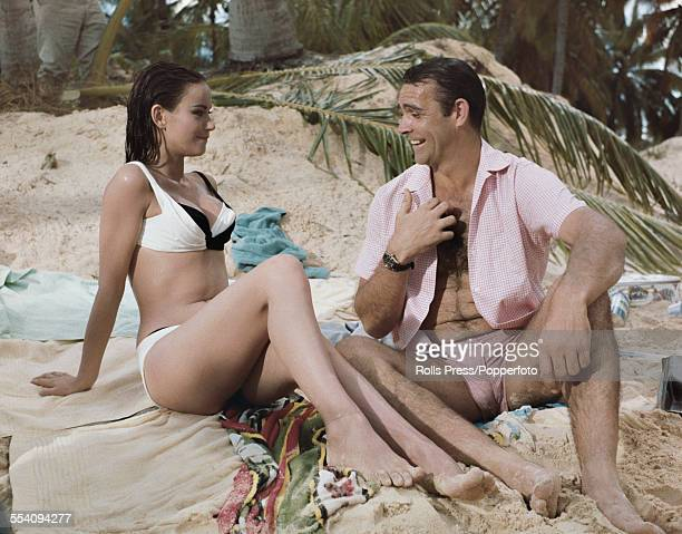 Scottish actor Sean Connery and French actress Claudine Auger pictured together wearing bathing costumes in a beach scene during production of the...