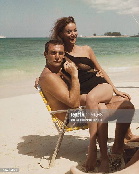 Scottish actor Sean Connery and French actress Claudine Auger pictured together wearing bathing costumes and sitting on a folding chair on a beach in...