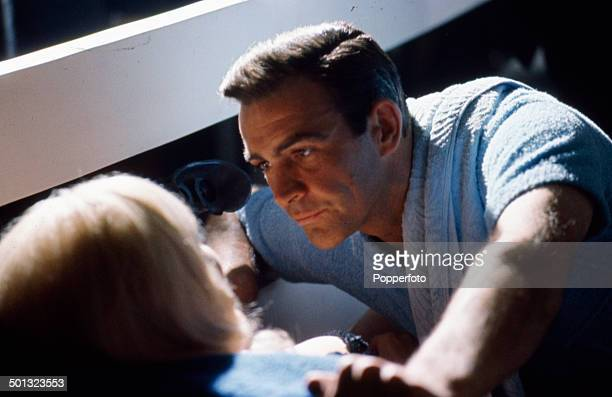 Scottish actor Sean Connery as 'James Bond' pictured with English actress Shirley Eaton playing 'Jill Masterson' in a scene from the film...