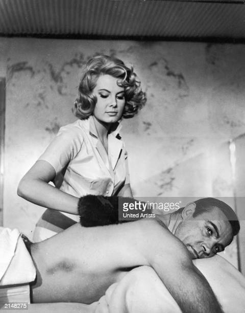 Scottish actor Sean Connery gets a massage from Molly Peters in a still from the James Bond film 'Thunderball' directed by Terence Young 1965