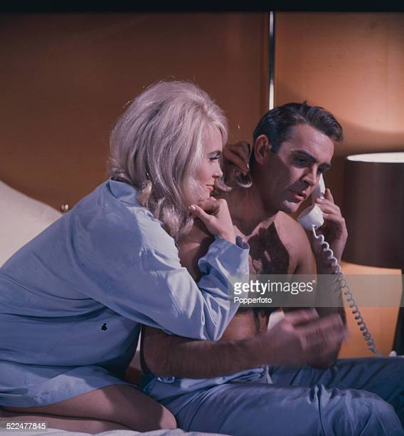 Scottish actor Sean Connery holds a telephone receiver to his ear as English actress Shirley Eaton looks on in character as Jill Masterson in a scene...