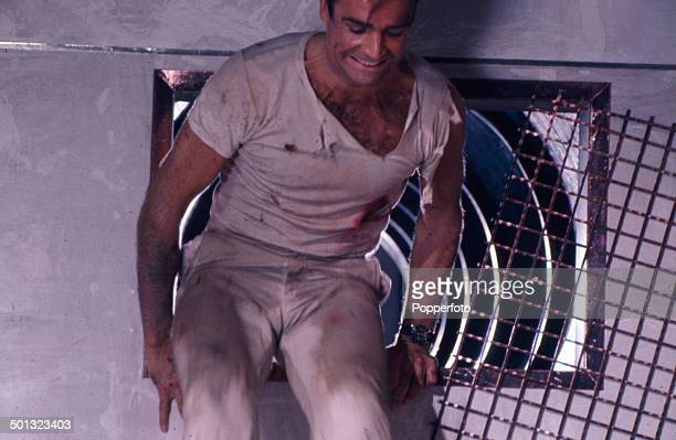 Scottish actor Sean Connery in character as 'James Bond' pictured climbing out of an air duct in a scene from the film 'Dr No' in 1962