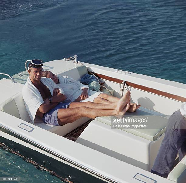 Scottish actor Sean Connery pictured sitting in the back of motor launch wearing blue shorts white towel and scuba mask with French actress Claudine...