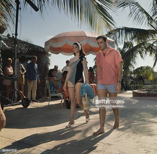 Scottish actor Sean Connery pictured walking with French actress Claudine Auger during filming of the James Bond film 'Thunderball' at a beach resort...