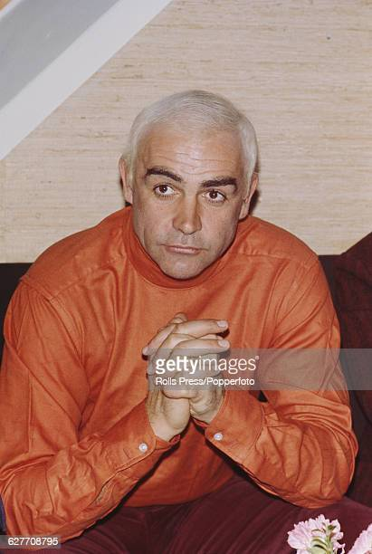 Scottish actor Sean Connery pictured with dyed white hair and wearing a bright orange shirt at a press conference to announce his role as Norwegian...
