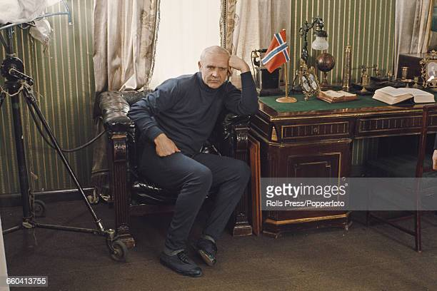 Scottish actor Sean Connery pictured with dyed white hair in character as Norwegian explorer Roald Amundsen sitting in a leather armchair beside a...
