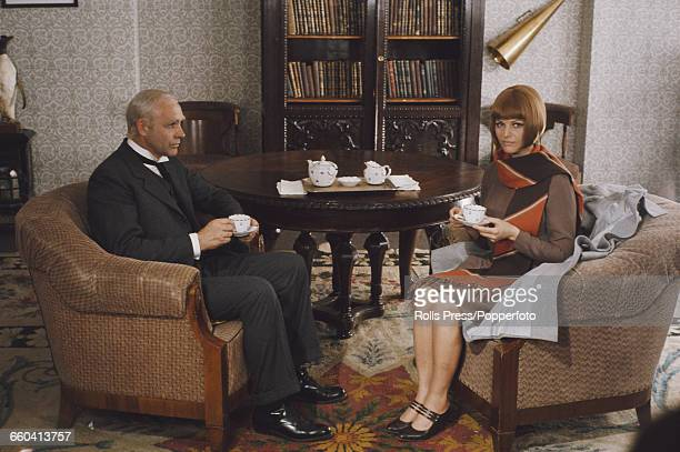 Scottish actor Sean Connery pictured with dyed white hair in character as Norwegian explorer Roald Amundsen sitting with Italian actress Claudia...