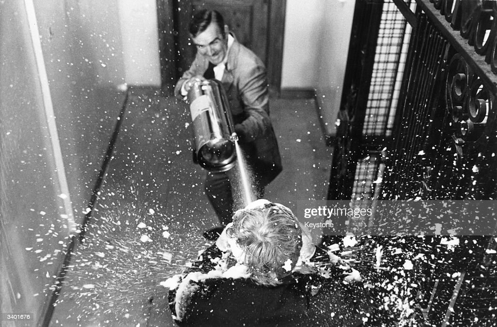 Scottish actor Sean Connery shoots an adversary with a jet of foam from a fire extinguisher in a scene from the James Bond film 'Diamonds Are Forever'.
