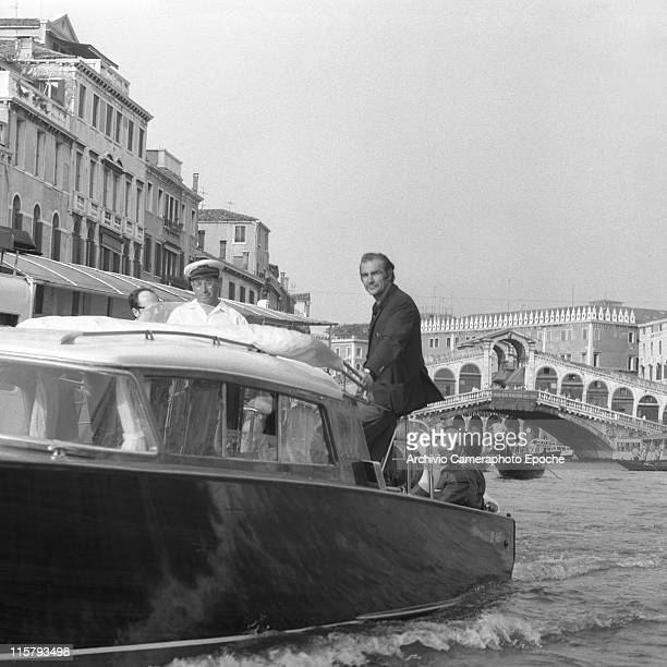 Scottish actor Sean Connery standing on a water taxi with others Rialto bridge and gondolas on the background Canal Grande Venice 1970s