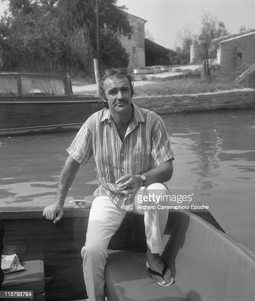 Scottish actor Sean Connery wearing a striped short sleeves shirt linen trousers slippers and sunglasses sitting on a water taxi with Torcello island...