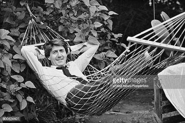 Scottish actor Tom Conti posed lying in a hammock in a garden in London on 27th June 1984