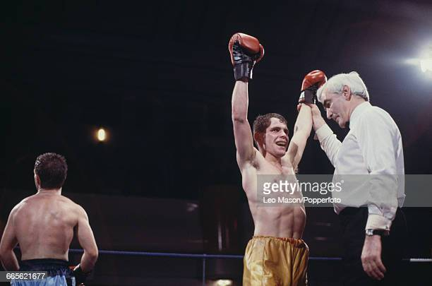 Scottish boxer Pat Clinton raises his arms in the air after defeating fellow Scottish boxer Joe Kelly to win the British flyweight title on a points...