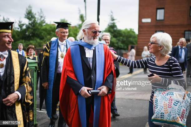 Scottish comedian and actor Sir Billy Connolly accompanied by Professor Sir Jim McDonald leave Barony Hall following receiving a honorary degree from...