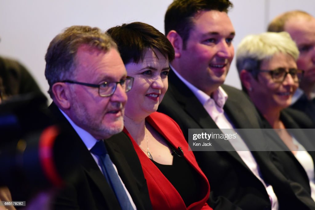 Scottish Conservative Party leader Ruth Davidson (C left), Scottish Secretary David Mundell (L), and Miles Briggs MSP (C right) listen to Prime Minister Theresa May speaking at the launch of the party's general election manifesto, on May 19, 2017 in Edinburgh, Scotland. A UK general election is to be held on Thursday June 8, 2017.