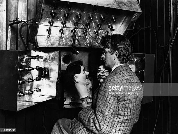 Scottish electrical engineer and television pioneer John Logie Baird demonstrating his new invention the television with the aid of two...