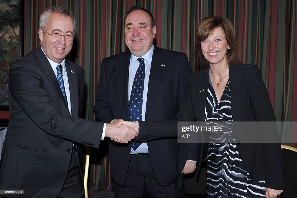 Scottish First Minister Alex Salmond (C) poses with head of French energy giant Areva Luc Oursel and Scottish Enterprise Chief Executive Lena Wilson on November 19, 2012 in Paris, after Areva group and Scottish Enterprise signed a memorandum of understanding on industrial site development for the manufacture of wind turbines in East Scotland. AFP PHOTO / ERIC PIERMONT