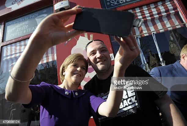 Scottish First Minister and SNP leader Nicola Sturgeon takes a selfie photograph with a supporter in the street as she campaigns for the UK general...