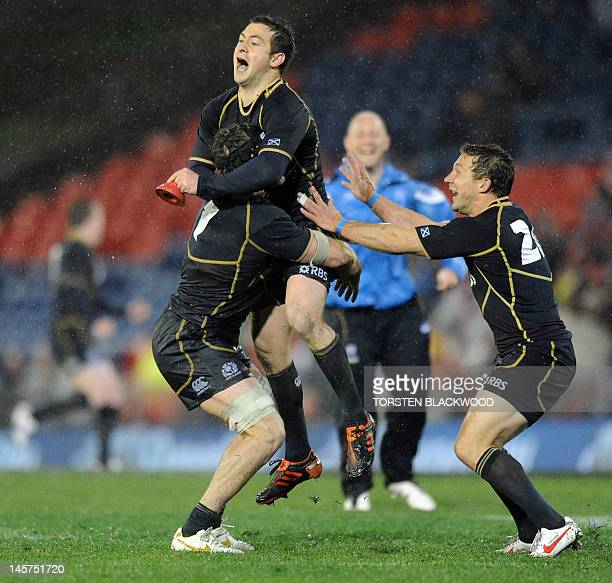 Scottish flyhalf Greg Laidlaw celebrates with teammates Ross Rennie and Chris Cusiter after kicking his third penalty goal of the game to deliver...