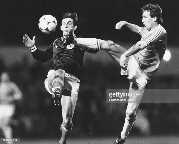Scottish football player Kenny Dalglish clashes with Welsh defender Joey Jones during the World Cup qualifying match at Hampden Park in Glasgow March...