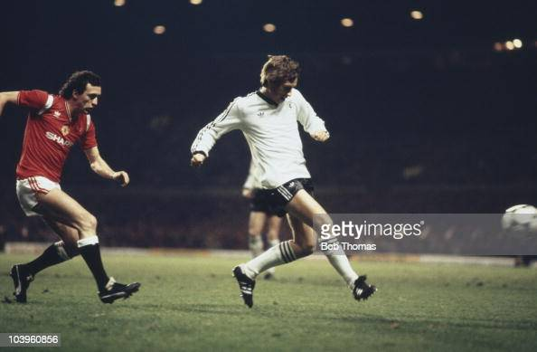 Scottish footballer Paul Sturrock of Dundee United takes a shot as Manchester United rightback John Gidman looks on during the UEFA Cup 3rd Round...