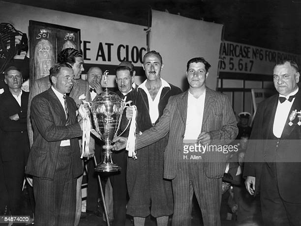 Scottish former footballer Alex James presents the Challenge Cup to T Finnegan winner of the News Of The World Individual Darts Championship finals...