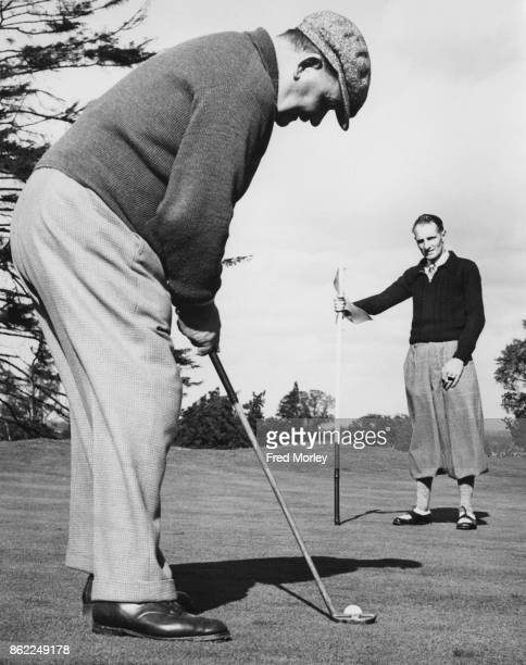 Scottish golfer Alexander Herd aka Sandy Herd during a round of golf at Moor Park UK 10th October 1938 His son Alex holds the flag in the background