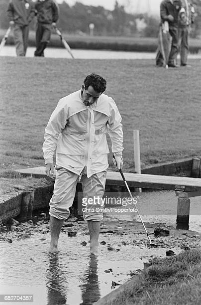 Scottish golfer Sam Torrance pictured bare footed as he stands in a stream of water to play a shot during action for Team Europe to win the 1985...