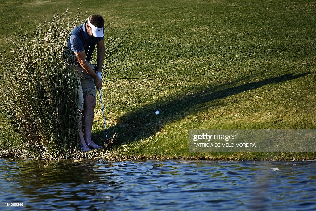 Scottish golfer Scott Jamieson plays a shot from the lake side to the 14th during the second day of the Portugal Masters golf tournament at Victoria...