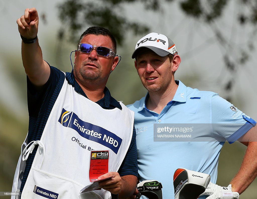 Scottish golfer Stephen Gallacher (R) talks with his caddie before teeing-off during the second round of the Dubai Desert Classic golf tournament in the Gulf emirate of Dubai on February 1, 2013. AFP PHOTO/MARWAN NAAMANI