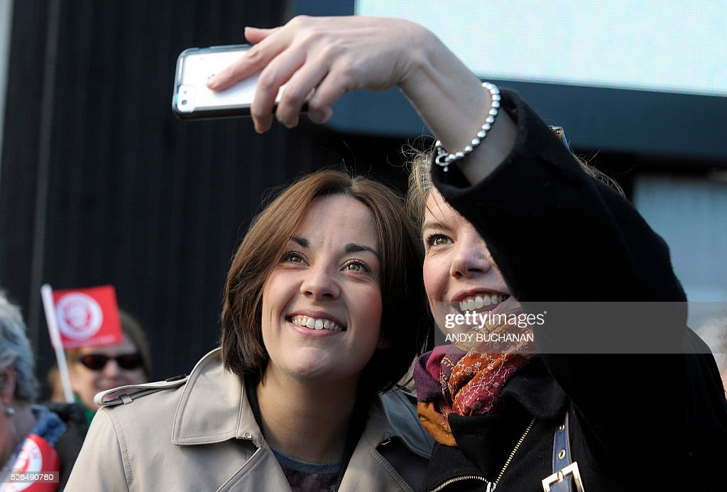 Scottish Labour leader Kezia Dugdale (L) poses for a selfie as she unveils a new election campaign poster on Leith Walk in Edinburgh on April 30, 2015. Scotland will elect a new national assembly on May 5, 2016 with First Minister Nicola Sturgeon's pro-independence Scottish National Party looking to tighten its stranglehold on power. The Conservatives are hoping to pile on the pain for Labour in their former fiefdom by replacing them as Scotland's main opposition. / AFP / Digital / Andy Buchanan
