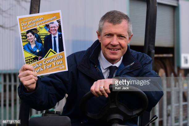 Scottish Liberal Democrat leader Willie Rennie holds up a copy of his party's manifesto for the Scottish local elections as he sits at the controls...