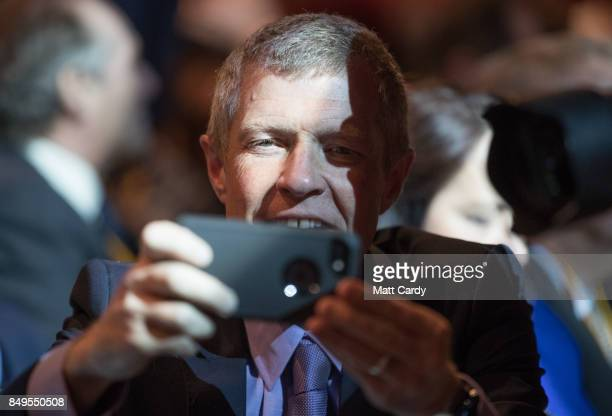 Scottish Liberal Democrat leader Willie Rennie takes a photograph as leader Vince Cable delivers his keynote speech during the final day of the...