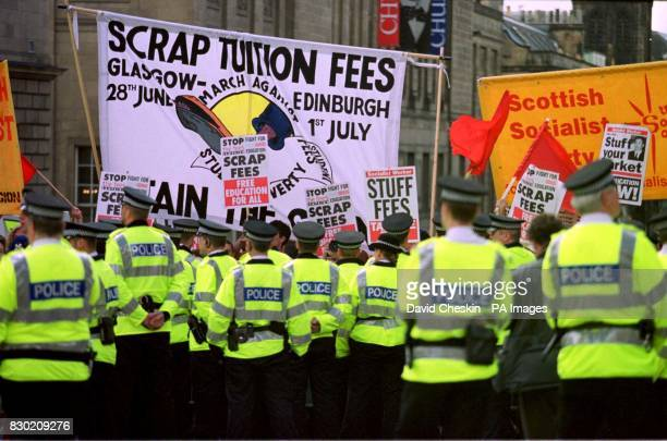 Scottish police hold back a demonstration against tuition fees as the the Queen travels up the Royal Mile in Edinburgh on her way to the State...