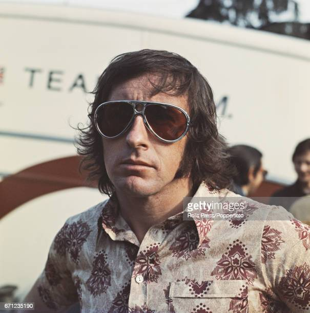 Scottish racing driver Jackie Stewart of the Elf Team Tyrrell posed wearing a pair of sunglasses at a motor racing circuit in 1971 the year in which...