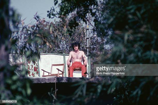 Scottish singer and guitarist Donovan pictured sitting in a chair and sunbathing at the Chaurasi Kutia ashram compound of Maharishi Mahesh Yogi near...