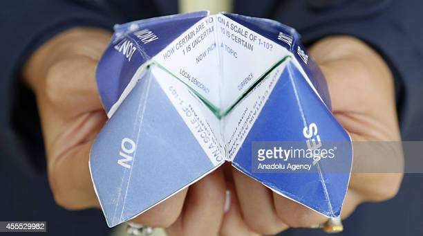 Scottish woman holds a paper fortune teller which Yes No Don't Care and Don't Know are written on at Referendum Cafe opening for demonstrating...