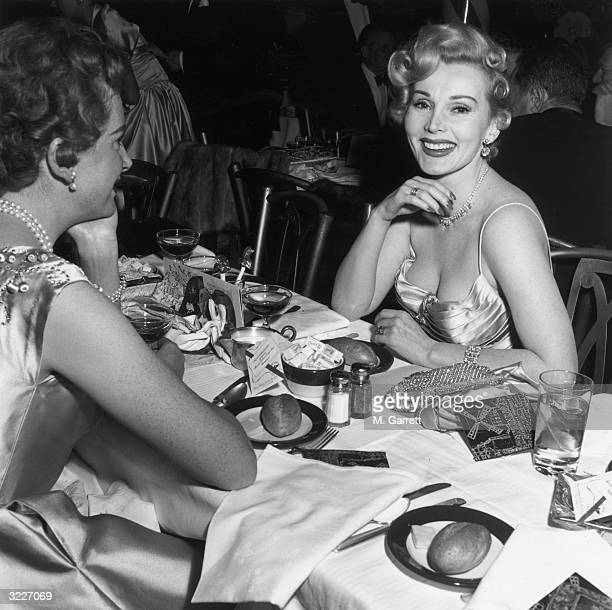 Scottishborn actor Deborah Kerr looking at Hungarianborn actor Zsa Zsa Gabor who is smiling at the camera as they sit across from each other at a...