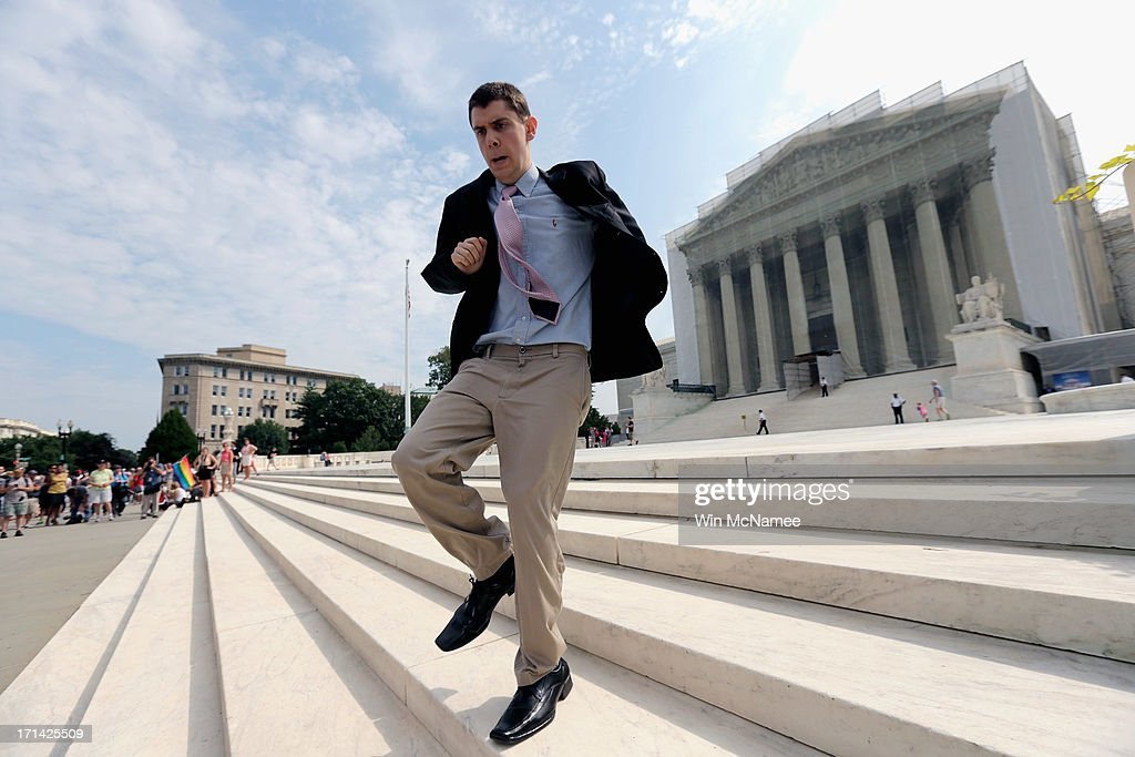 Scotusblogcom intern Dan Stein runs with news of affirmative action ruling front of the US Supreme Court building June 24 2013 in Washington DC The...