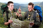 Two young scout boys with backpacks holding the map and showing the right way traveling in the mountains