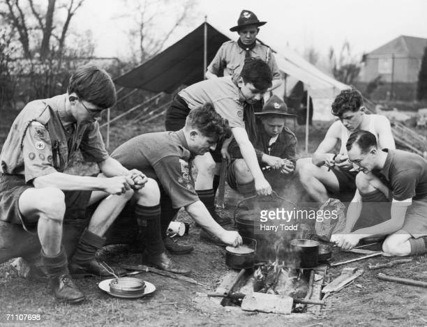 Scouts and Sea Scouts from London and the home counties cooking over a fire at a weekend rally in Raynes Park SouthWest London 4th April 1943