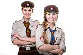 Two young scout girls standing together in hat and uniform isolated on white background