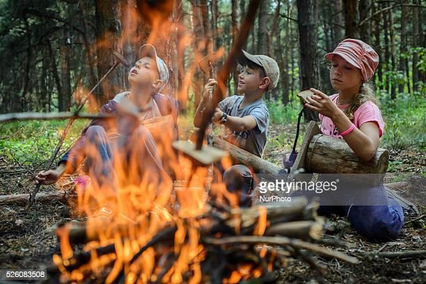Scouts roasting bread over campfire in a hike Ukrainian scout training camp Kiev region Ukraine