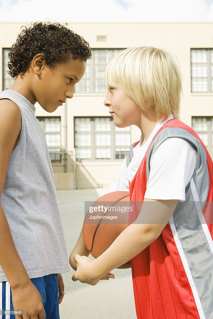 Scowling boys with basketball : Stock Photo