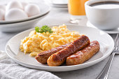 A plate of delicious scrambled eggs and breakfast sausage with coffee and orange juice.