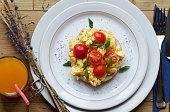 Scrambled eggs and tomato on bagel with a glass of juice