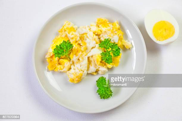 Scrambled eggs On white plate and hard-boiled egg