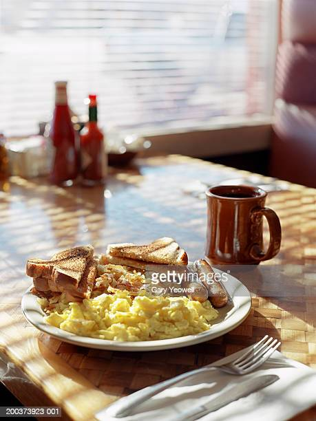 Scrambled eggs, sausages, hash brown, toast and coffee, close up