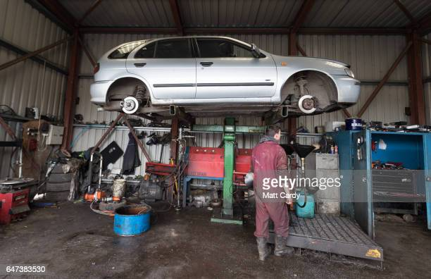 A scrap car is drained of fluids and oil as it is processed at Pylle Motor Spares and Metal Processing a licensed scrap yard in Pylle near Shepton...