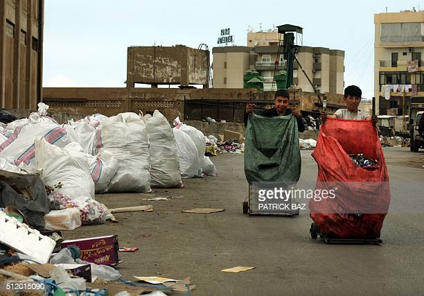 Scrap collectors race with their karts next to a temporary garbage dump in the town of Jdeideh north east of the Lebanese Beirut on February 24 2016...